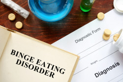 binge eating disorder written on book with tablets.