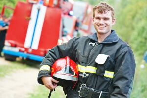 young smiling fireman firefighter in uniform in front of fire en